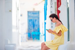 Woman with smartphone outdoors on the narrow old street. Tourist using mobile smartphone.