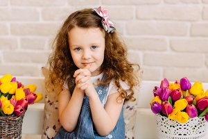 Portrait of litlle girl among flowers bouquets