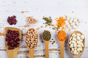 Selection of colorful beans on white wood background
