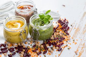 Selection of colorful hummus in jars