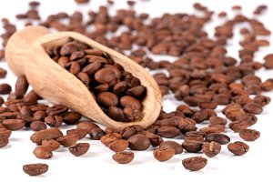 coffee beans in a wooden scoop isolated on white background