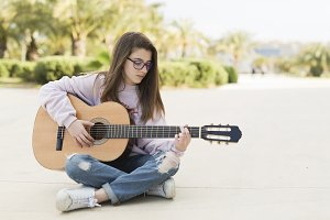 Teenager sitting playing guitar