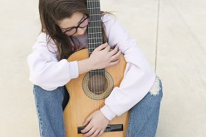 Teenager sitting with her guitar