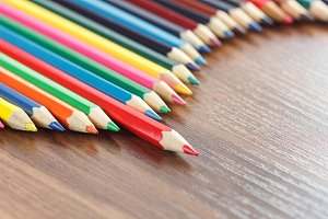 Set of colored pencils, wooden background