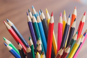 Set of colored pencilsin the glass, wooden background