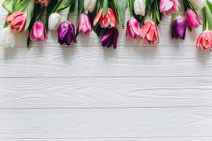 Fresh tulips on the wooden table.