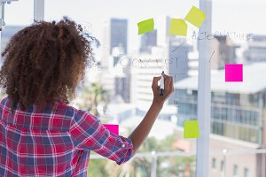 Woman drawing on flowchart with sticky notes