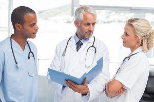Three doctors examining a file