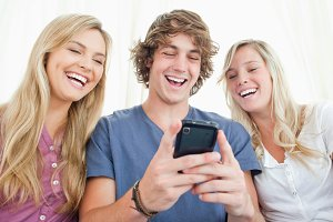 Three friends looking at the screen of a mobile phone while smiling