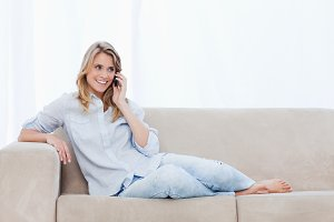 A woman on a couch is talking on her mobile phone