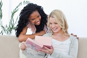 Two smiling women look at a present inside a pink box