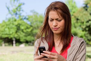 Young woman with a concerned expression reading a text message