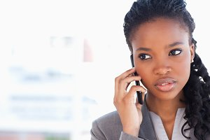 Young employee looking towards the side while talking on the phone