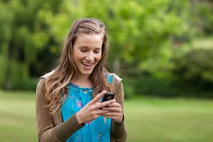 Happy teenage girl receiving a text on her mobile phone
