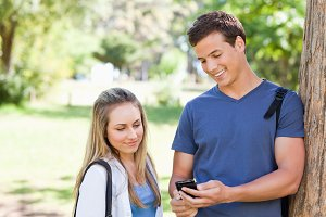 Close up of a student showing his smartphone screen to a girl
