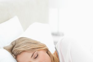 Woman sleeping in bed with hands and head resting on the pillow