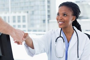 Female doctor shaking a hand