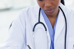 Portrait of a female doctor writing a prescription