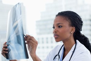 Focused female doctor looking at a set of Xrays