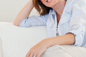 Smiling woman sitting on sofa