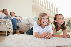 Siblings lying on the carpet watching tv