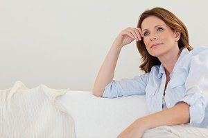 Mature woman in thoughts on couch