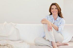 Smiling mature woman sitting on sofa