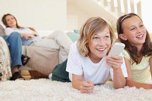 Siblings lying on the floor watching tv