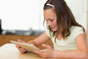 Girl at kitchen table looking at tablet