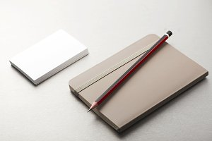 Pencil, business card and notepad on gray background. Business and education.