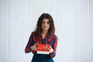 Holiday time. Portrait of elegant young girl take or give gift in beautiful red box. Portrait of attractive Curly woman look to the camera and propose the present. Christmans concept.
