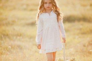 Blond little girl on the sunset.