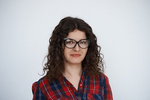 Young attractive smiling Curly hair programmer woman in trendy glasses dressed in check shirt look to the camera. Talanted manager with long hair portrait on neutral background feel good. Happyness concept.