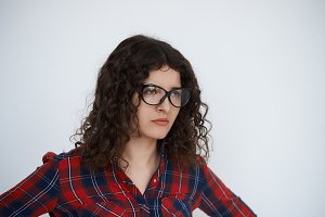 Stylish dressed brunette woman look away on neutral white background. Close up portrait of serious female.Curly hair Girl ready to scold somebody. Unhappy emotion on the face.