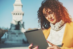 Curly woman with digital tablet