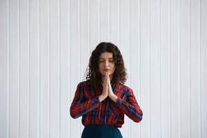 Meditation and relaxation concept. Curly Woman keep hands together as pray. Pretty girl collect positive energy for improve health. Cope space for advertising yoga product for managers from office.