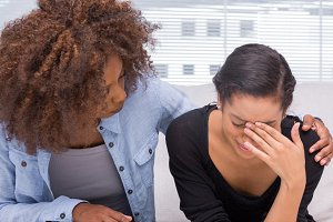 Sad woman crying next to her therapist