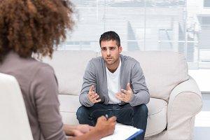 Depressed man speaking to a therapist