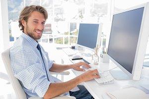 Smiling designer working at his desk