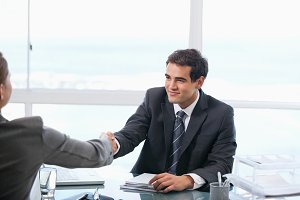 Businessman shaking hands with a client while sitting