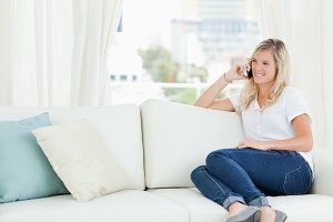 A smiling woman sitting on the couch as she talks on her phone
