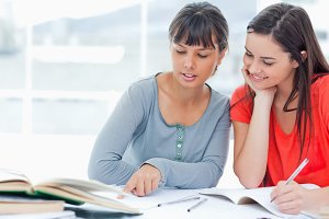 Two girls help one another as they study