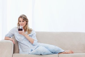 A woman lying on a couch is holding a glass of red wine