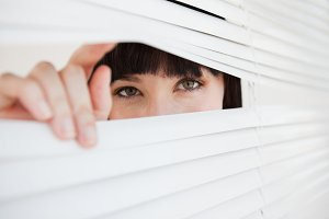 Woman opening a part of closed blinds with her fingers