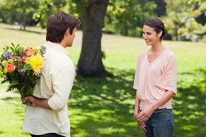 Woman smiling as her friend approaches her with flowers