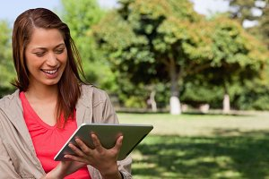 Young woman smiling enthusiastically while using a tablet