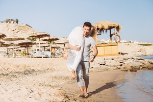 A guy carrying a girl, at the beach