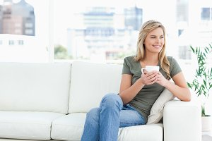 Woman sitting on the couch, with mug in hand, smiling and looking sideways