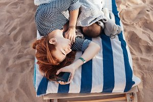 Mom and baby on the beach sleeping