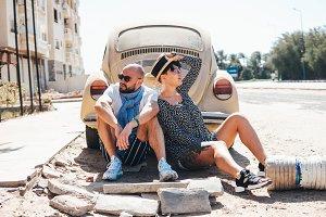 Couple sitting on the asphalt behind the car